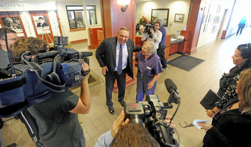 Gov. Paul LePage has a light moment with physician Joyce M. Stein in the lobby of Inland Hospital during a press conference in Waterville on Wednesday. LePage made the appearance to announce repayment of state MaineCare debt to Maine's 39 hospitals, including $9.5 million to Inland Hospital.