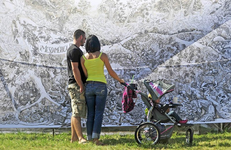 Nate Sprague, left, and Madeleine Hill, center, with her 2-year-old daughter, London Wallace, view the MesoAmerica drawing by the Beehive Design Collective on display at the Common Ground County Fair in Unity today.