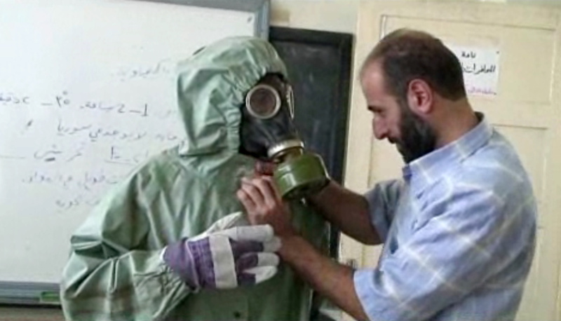 A volunteer adjusts a gas mask and protective suit on a student during a classroom session on how to respond to a chemical weapons attack in Aleppo, Syria. The drills came amid continued diplomatic wrangling over how to collect Syria's arsenal of chemical and biological agents.