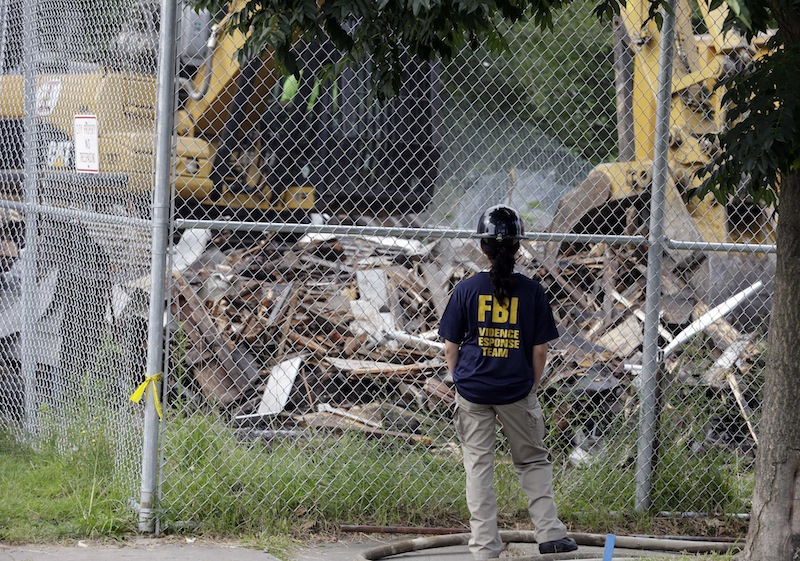 In this Aug. 7, 2013 file photo, an FBI agent watches as the Cleveland home of Ariel Castro, where three women were held captive and raped for more than a decade, was demolished. Castro, 53, now serving a life sentence for the kidnapping and rapes, was found hanging in his cell, Tuesday night, Sept. 3, 2013, at the Correctional Reception Center in Orient, Ohio. (AP Photo/Tony Dejak, File)