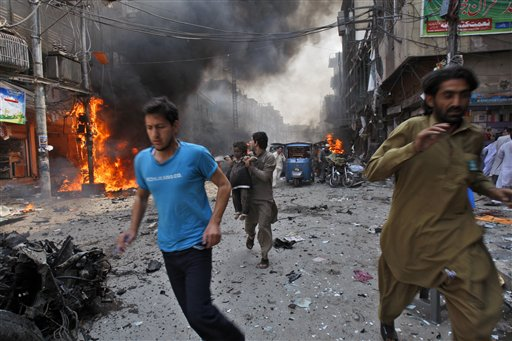 Pakistani run away from the site of a blast shortly after a car explosion in Peshawar, Pakistan, Sunday, Sept. 29, 2013. A car bomb exploded on a crowded street in northwestern Pakistan Sunday, killing scores of people in the third blast to hit the troubled city of Peshawar in a week, officials said.