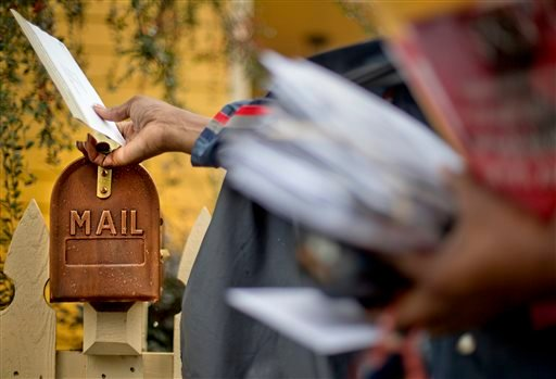 U.S. Postal Service letter carrier Jamesa Euler delivers mail in Atlanta. The post office expects to lose $6 billion this year and is seeking help from Congress to fix its finances.