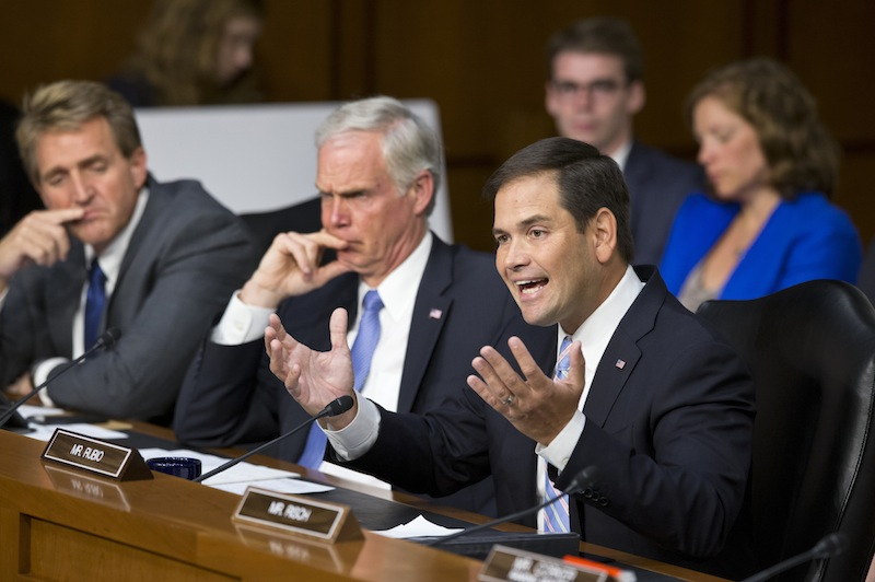 Senate Foreign Relations Committee member Sen. Marco Rubio, R-Fla., joined by fellow committee members, Sen. Ron Johnson, R-Wis., center, and Sen. Jeff Flake, R-Ariz., questions Secretary of State John Kerry during committee's hearing on President Barack Obama's request for congressional authorization for military intervention in Syria, a response to last month's alleged sarin gas attack in the Syrian civil war, Tuesday, Sept. 3, 2013, on Capitol Hill in Washington. (AP Photo/J. Scott Applewhite)
