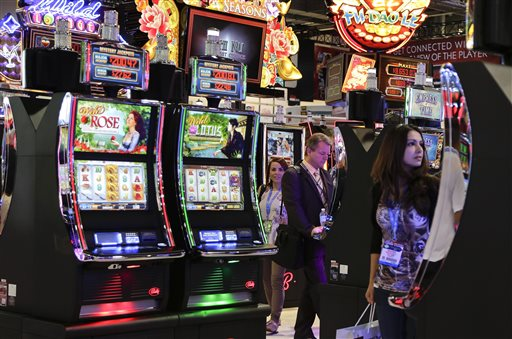 Gaming industry representatives stop to play various slot machines at the Global Gaming Expo on Wednesday in Las Vegas. Moving away from moving parts to video technology, the venerable slot machine is undergoing a generational shift.