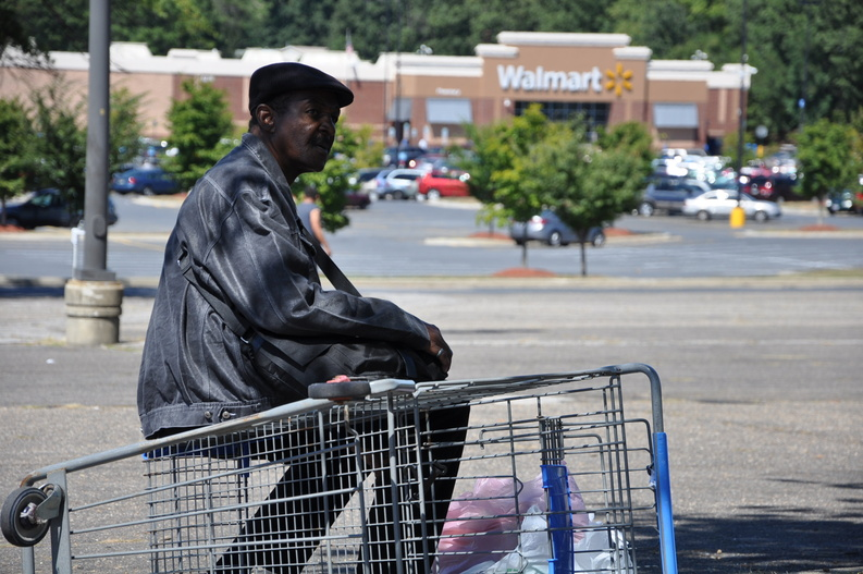 Washington resident Jimmy Pegues, 64, rests on an overturned shopping cart recently after crossing the parking lot of the Walmart store in Landover, Md. The round-trip bus trip from his apartment takes half a day, but Pegues said it is worth it, saving him roughly $110 a month on heart medications and blood thinners through Walmart's $4 generic prescription drug program. Jimmy Pegues Wal-Mart