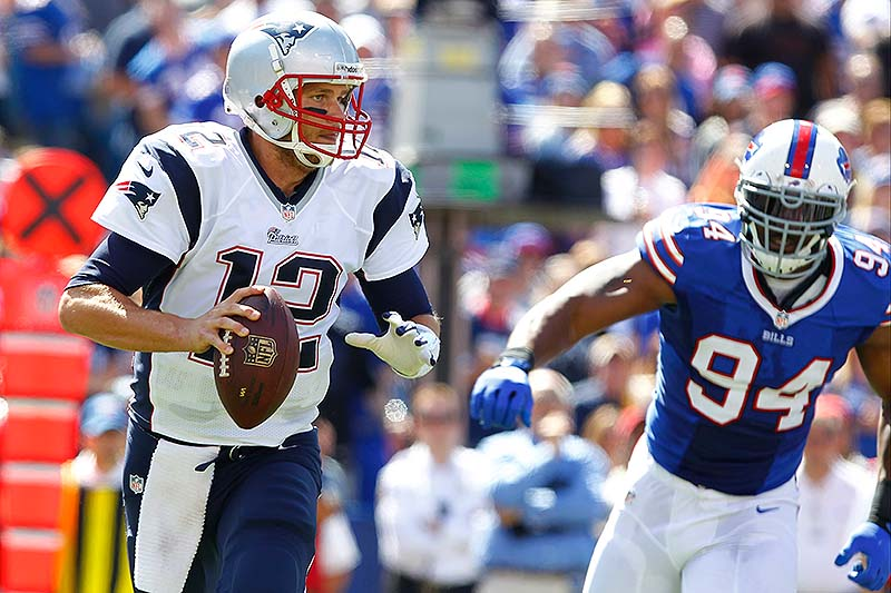 Patriots QB Tom Brady looks to pass as Buffalo's defensive end Mario Williams closes in during Sunday's game at Orchard Park, N.Y.