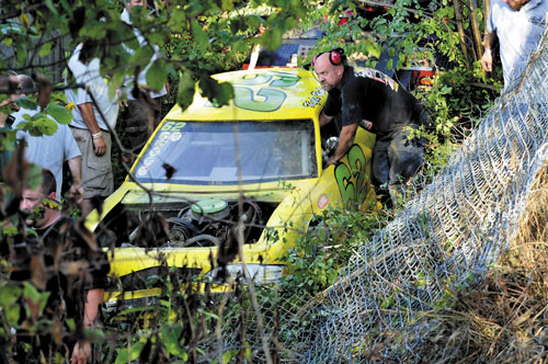 CRASH AND GO: Workers clear a fence and trees from the race car driven by Kyle Robinson, 15, of Clinton that went off the track, up a steep dirt embankment, through a wire fence and landed in a ditch Sunday at Unity Raceway. Robinson was not hurt and returned to race after repairs to the car were made.