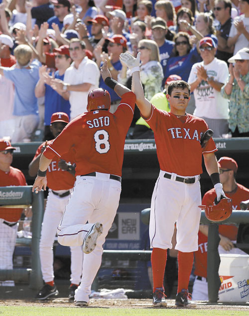 NICE JOB: Texas' Geovany Soto (8) is congratulated by Ian Kinsler, right, at the dugout entrance after Soto scored on a Craig Gentry single against the Los Angeles Angels on Sunday in Arlington, Texas. A.J. Pierzynski also scored on the single by Gentry.