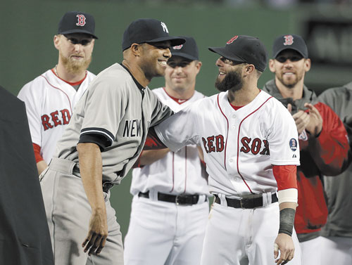 CONGRATULATIONS: New York Yankees relief pitcher Mariano Rivera, left, embraces Boston Red Sox's Dustin Pedroia, right, during a tribute to Rivera before the start of Sunday night's game at Fenway Park in Boston.