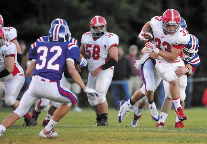 BIG GAIN: Cony High School running back Reid Shostak, 33, gets tangled up with Messalonskee High School's Jake Dexter in the first quarter Friday at Messalonskee High School in Oakland.