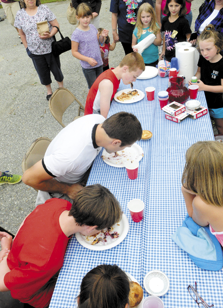 Spectators watch the pie-eating contest during Whitefield Community Day today in Whitefield. Tyler Pope, 32 of Whitefield, center, in white shirt, was the fastest of four contestants to eat three Table Talk pies without using his hands.