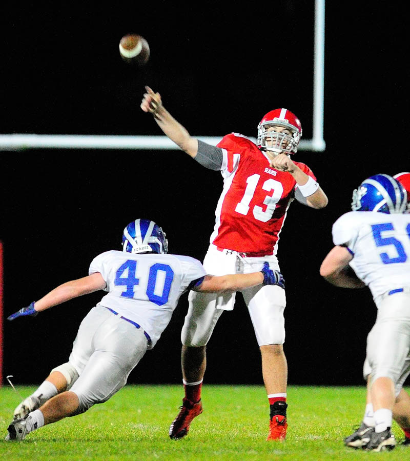 Cony quarterback Ben Lucas, middle, throws a touchdown pass under pressure from Lawrence's Cole Robinson, left, and Kyle McLain during a game on Friday September 27, 2013 at Alumni Field in Augusta. He completed a a 37 yard touchdown to Jonathan Saban.