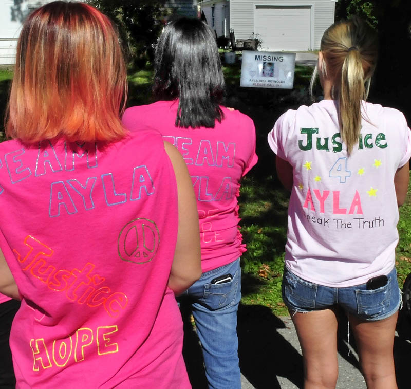 Wearing T-shirts in honor of Ayla Reynolds today, three of about two dozen participants in a walk pray for the missing toddler at the Violette Avenue home where she was reported missing in December 2011. In the background is a photograph of Ayla Reynolds.