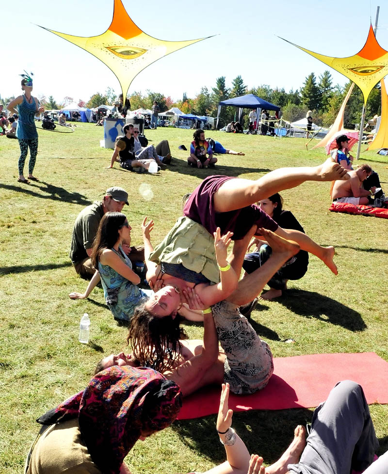 Yoga instructor Denise Porter Kemp is held up by Dave Melnick while doing partner acrobatics, as music played during the Great North Fest in Norridgewock today. Organizers estimated 1,500 people attended the three-day event.