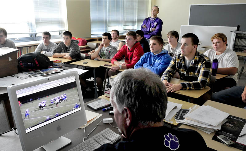 PLAYBACK: Waterville football offensive coordinator Ken Lindlof monitors a game video as players and head coach Frank Knight, standing, watch it on a larger screen Wednesday at the high school.