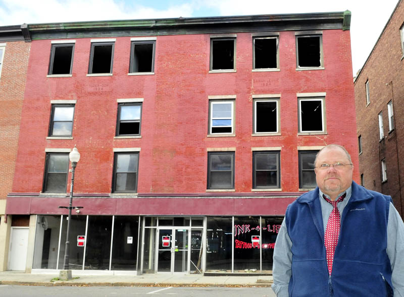 John Weeks on Wednesda stands in front of his downtown Waterville building on Main Street that was destroyed by fire in May. Weeks says he plans to raze the structure and possibly build another at the site.
