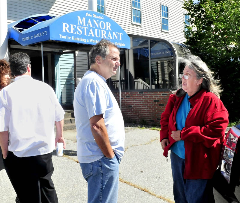 Peter Martin, whose family owned the former John Martin's Manor in Waterville, speaks with long-time employee Amanda Proctor outside the business at today's auction of the property.