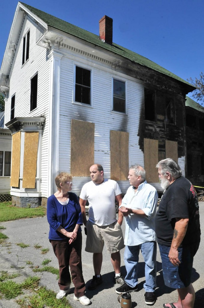 These Elm Court residents are concerned about the standing remains of this burned out home that was destroyed by a fire August 25 in Waterville. Authorities have determined it was set intentionally. From left are Patricia Farnsworth, Randy Frappier, Wes Berry and Chris Carpenter.