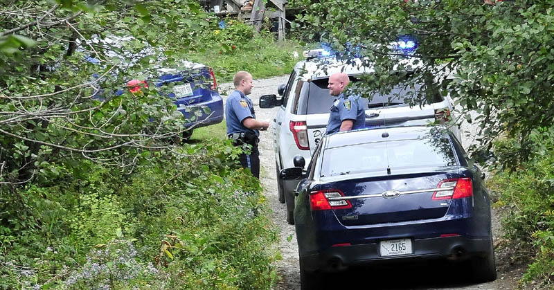 Madison and Skowhegan police gather on Monday near a car, at left, that was reportedly stolen in Madison and then later abandoned in Skowhegan after a high-speed chase. The driver of the car was arrested.