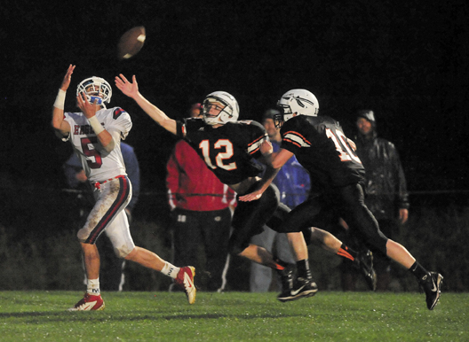 Messalonskee's Devin Warren, 5, makes a touchdown reception over Skowheganl defenders Owen Mercier, 12, and Adam Clukey in the first quarter Friday night in Skowhegan. The Indians won the game 14-6.