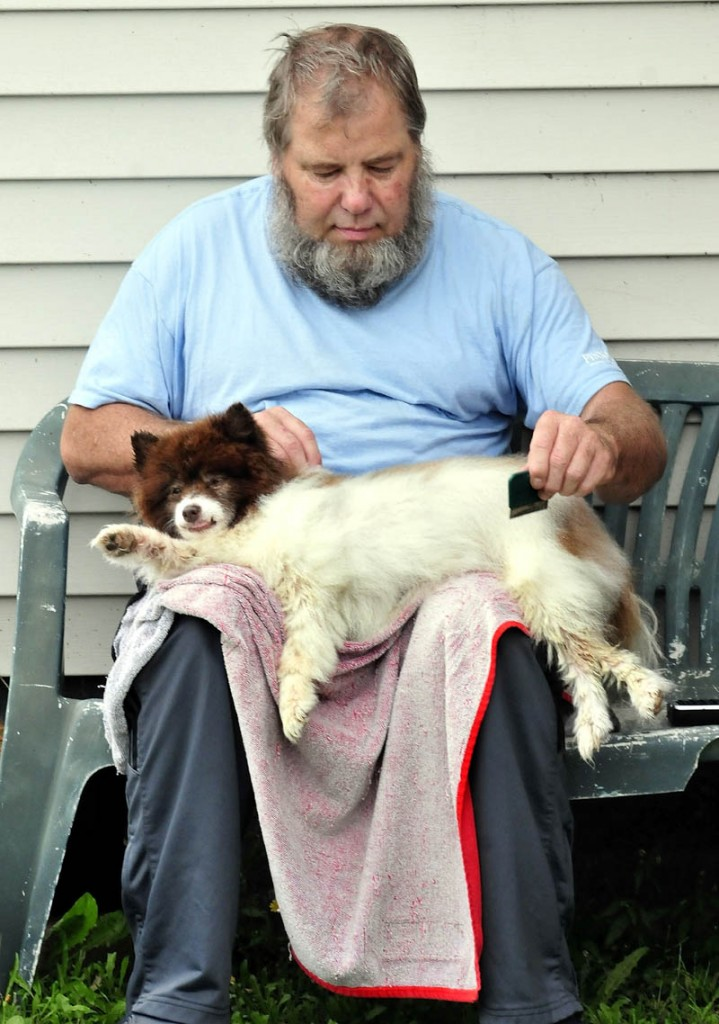 Coco the dog relaxes in the lap of Cecil Parsons as he combs the dog's hair in Waterville recently.