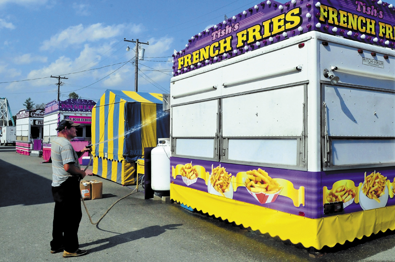 Enrique Gonzales washes down the exterior of Tish's Fries food stand at the Franklin County Fairgrounds in Farmington on Wednesday. The Farmington Fair begins this Sunday.