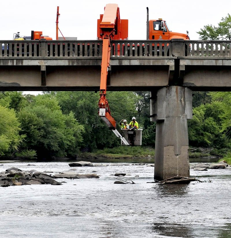 Maine Department of Transportation workers inspect the condition of the underside of the Harry Bridge over Sandy River in Farmington Falls today.