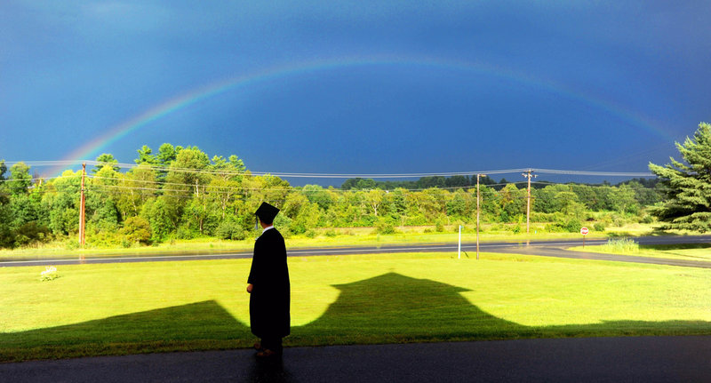 Cody Buzzell, 17, stands in the shadow of Moody Chapel as a rainbow shines over the Maine Academy of Natural Sciences during the charter school's first commencement event, held last month at the former Good Will-Hinckley School campus in Fairfield.