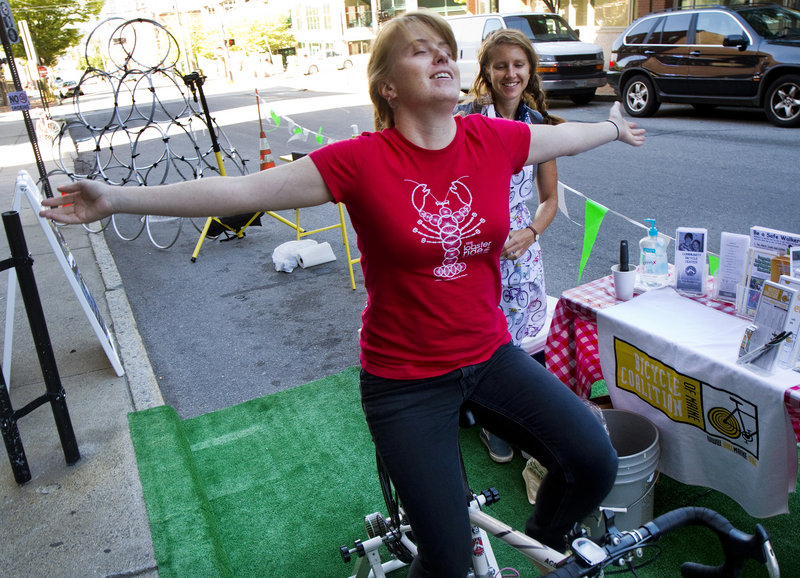 Elizabeth Hall of the Bicycle Coalition of Maine enjoys a peddle in a parking space outside the organization's Preble Street office, during Portland's second annual Park(ing) Day on Friday, September 20, 2013. Taking place in nearly 200 cities around the world, people take over parking spaces for to hang out and have fun.