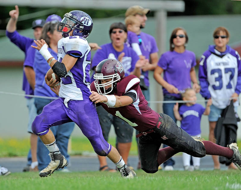 Waterville's Dalton Denis, left, breaks the grasp of Nokomis' Ray Girroir on his way to a touchdown on a punt return Saturday at Nokomis High School in Newport.