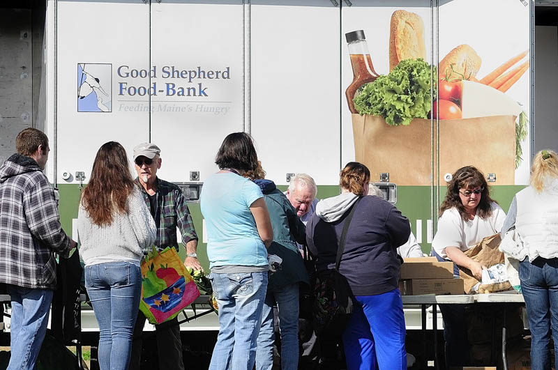 Volunteers hand out food during a Good Shepherd Food Bank food mobile event on Friday at Mill Park in Augusta.