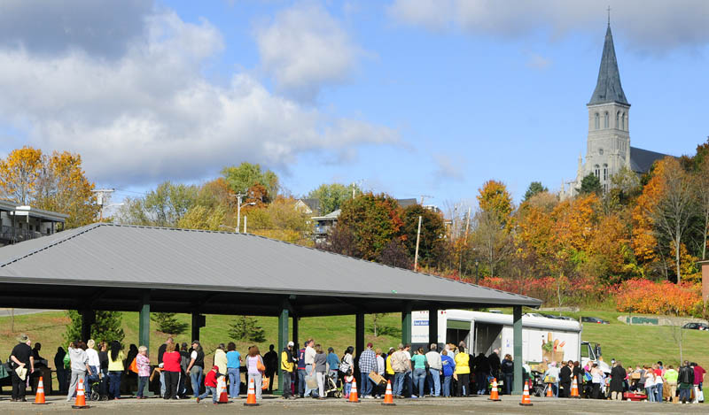Hundreds of people stand in line during a Good Shepherd Food Bank food mobile event on Friday at Mill Park in Augusta.