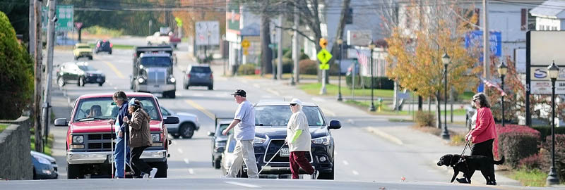 People cross at Bangor Street at the Murray Street intersection during a walk held to raise awareness of white canes and guide dogs today in Augusta.