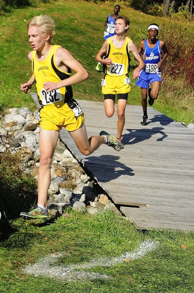 Maranacook's Jason Stevenson, (232), left, and Austin Landry (227) run over a bridge during the KVAC cross country championships on Saturday October 19, 2013 at Cony High School in Augusta.