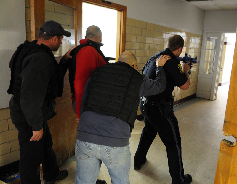 Augusta firefighter/paramedics Shawn Stevens, left, Scott Sirois, wearing a red jacket, and Rich Beaudoin stay low and close to the wall, as they follow Augusta Police patrolman Ben Murtiff down a hallway during a simulated school shooting incident Friday at the former Hodgkins middle school in Augusta.