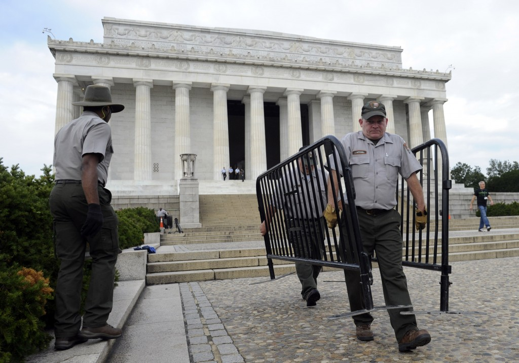 National Park Service employee James Mitchell, right, and others remove barricades from the grounds of the Lincoln Memorial in Washington on Thursday. Barriers went down at National Park Service sites and thousands of furloughed federal workers returned to work throughout the country Thursday after 16 days off the job because of the partial government shutdown.