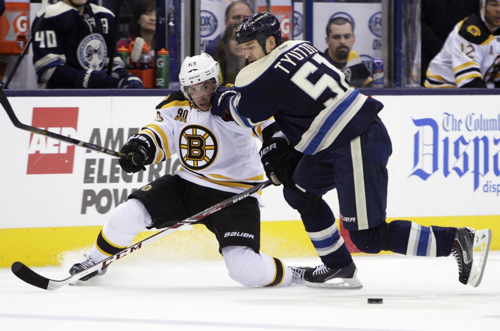 Columbus Blue Jackets' Fedor Tyutin, right, checks Boston Bruins' Brad Marchand away from the puck in the first period Saturday at Columbus, Ohio.