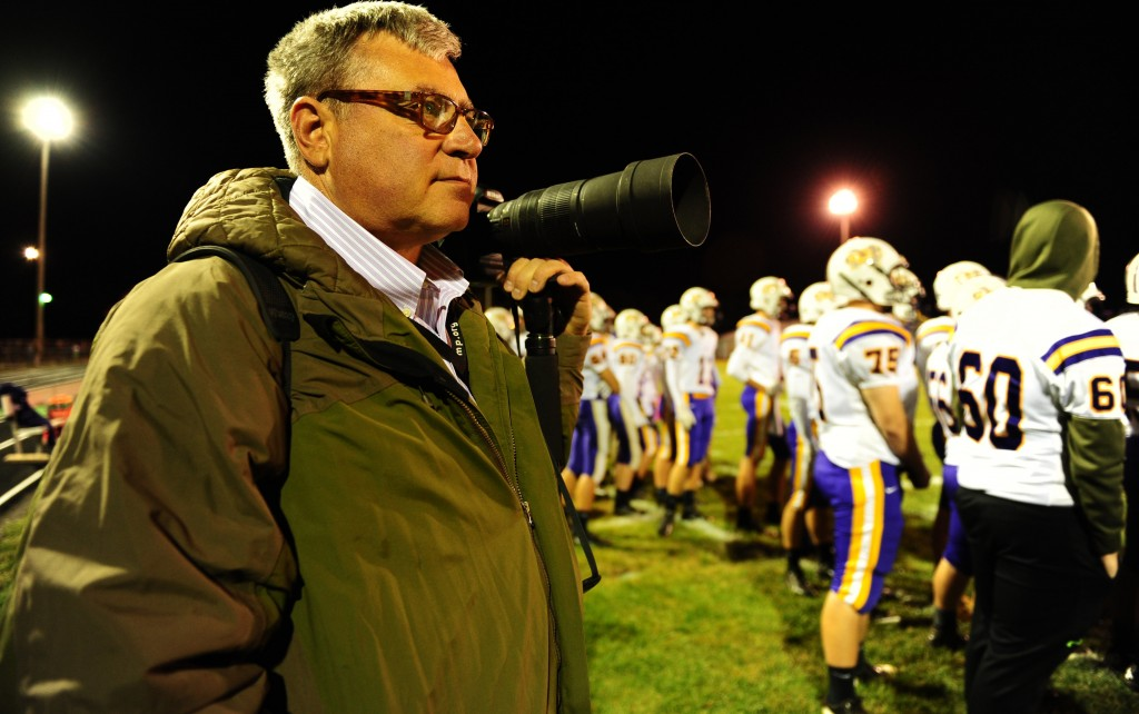 Self-employed photographer Michael Weaver works the sidelines of a high school football game in Jerseyville, Ill., on Friday night. It took him about a week and a half, but Weaver kept going back to the HealthCare.gov website until he opened an account and applied for a tax credit that will reduce his health care premiums. For the first time Sunday, the White House appealed for people to report their interactions with the exchange.