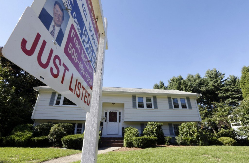 """A """"For Sale"""" sign hangs in front of a house in Walpole, Mass., recently. Nationwide, average home prices are still 22 percent below their April 2006 peak."""