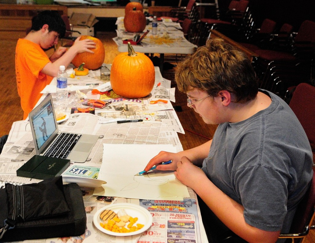 Pumpkin Carving: Corey Boynton, top left, carves a pumpkin while Everett Hotham draws during the After School Art Program on Wednesday at Johnson Hall in Gardiner.