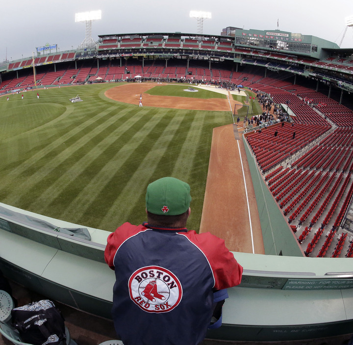 A Boston Red Sox fan watches during batting practice before Game 1 of baseball's World Series between the Red Sox and St. Louis Cardinals Wednesday, Oct. 23, 2013, in Boston.