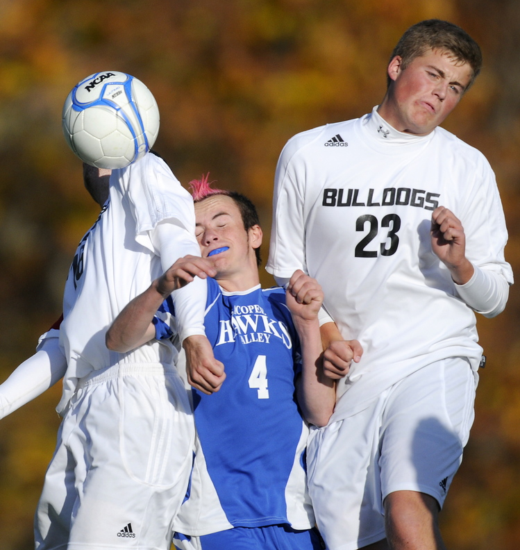 TIGTH QUARTERS: Hall-Dale High School's Konnor Longfellow, left, and Ryan Sinclair sandwich Sacopee Valley High School's Devin Day during the Bulldogs' 2-0 win over Sacopee Valley in a Western C quarterfinal Wednesday in Farmingdale.