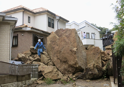 A fire fighter walks over rocks fallen from a cliff over a garage and a road in a residential area in Kamakura, southwest of Tokyo, after a powerful typhoon hit Japan's metropolitan area Wednesday morning, Oct. 16, 2013. Typhoon Wipha triggered landslides and caused multiple deaths on a Japanese island off Tokyo, before sweeping up the country's east coast, grounding hundreds of flights and paralyzing public transportation in Tokyo during Wednesday morning's rush hour.