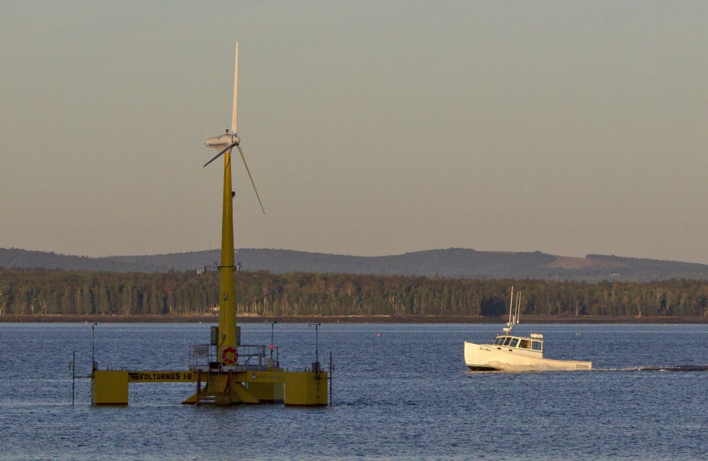 A lobster boat passes a floating wind turbine off the coast of Castine in September. The University of Maine's 9,000-pound prototype has been generating power since the summer.