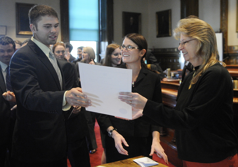 Winthrop native Tavis Hasenfus, left, accepts his certificate of admission to the Maine Bar from Kennebec County Superior Court deputy administrative clerk Penny Moore during a ceremony Monday at the Augusta court for new attorneys practicing in Maine.