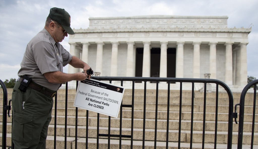 A National Park Service employee posts a sign on a barricade to close access to the Lincoln Memorial in Washington on Tuesday. Congress plunged the nation into a partial government shutdown Tuesday as a long-running dispute over President Barack Obama's health care law stalled a temporary funding bill, forcing about 800,000 federal workers off the job and suspending most non-essential federal programs and services.