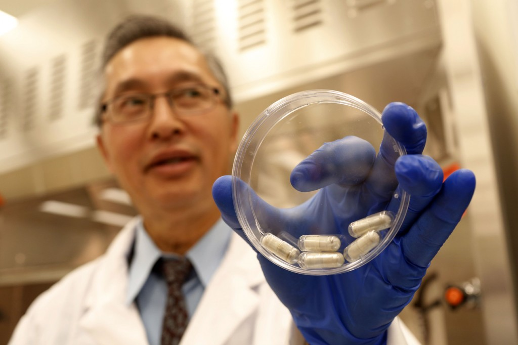 Dr. Thomas Louie, an infectious disease specialist at the University of Calgary, holds a container of stool pills in triple-coated gel capsules in his lab in Calgary, Alberta, Canada, last month.