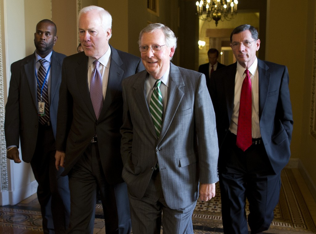 Senate Minority Leader Sen. Mitch McConnell, R-Ky., center, walks with Sen. John Cornyn, R-Texas, left, and Sen. John Barrasso, R-Wyo., to the Senate floor on Capitol Hill on Monday, Oct. 14, 2013 in Washington. The federal government remains partially shut down and faces a first-ever default between Oct. 17 and the end of the month.
