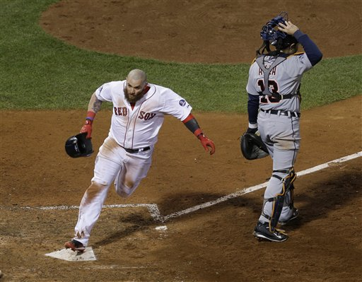 Boston Red Sox's Jonny Gomes scores the winning run on a hit by Jarrod Saltalamacchia during Game 2 of the American League baseball championship series against the Detroit Tigers Sunday, Oct. 13, 2013, in Boston. At right is Detroit Tigers' Alex Avila. (AP Photo/Matt Slocum)