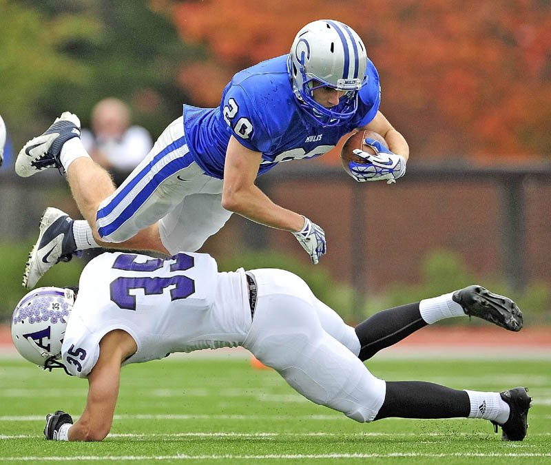 UP AND OVER: Colby College's Thomas Brewster dives over Amherst College defender Christopher Dow during the Mules' 14-10 loss Saturday at Colby College in Waterville.